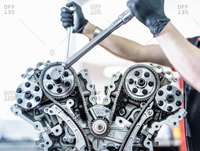 Engineer working on engine in racing car factory, close up