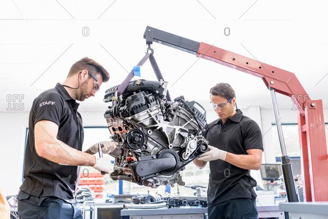 Engineers working on engines in racing car factory