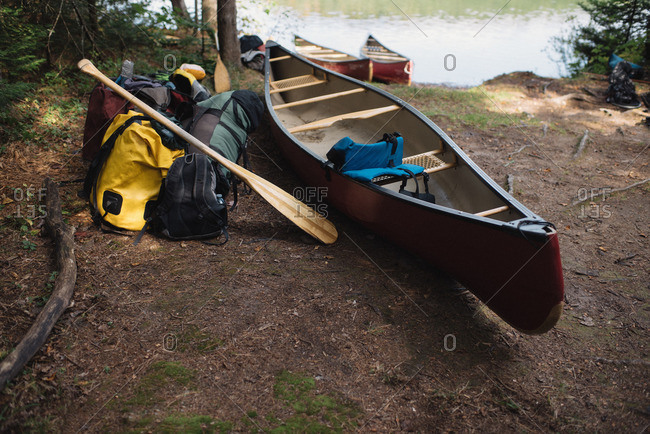 Canoe and camping equipment beside lake, Algonquin, Ontario, Canada