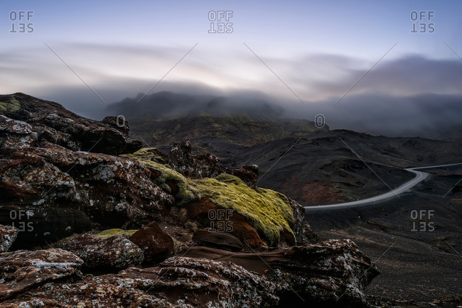 Distant view of winding road with mist over mountain tops, Kleifarvatn, Iceland