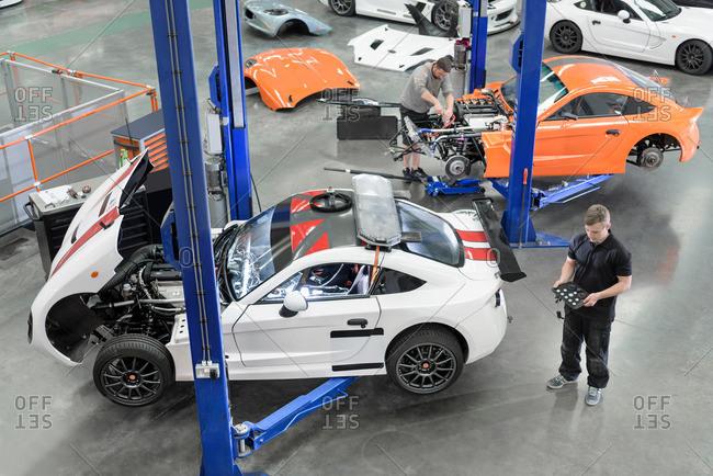 Garforth, UK - May 10, 2016: Engineer repairing racing cars in factory