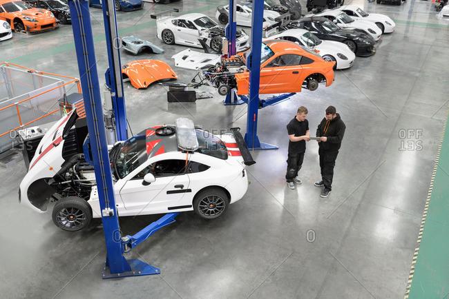 Garforth, UK - May 10, 2016: Engineer repairing racing cars in racing car factory