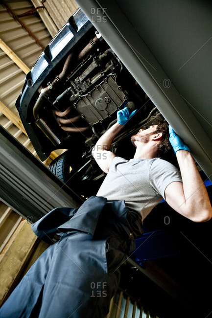 Male mechanic checking engine of car from underneath the vehicle
