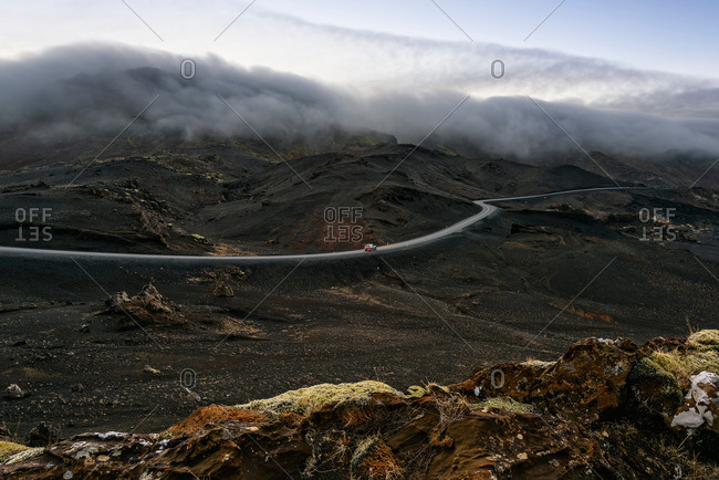 Distant view of car on winding road with mist over mountain tops, Kleifarvatn, Iceland