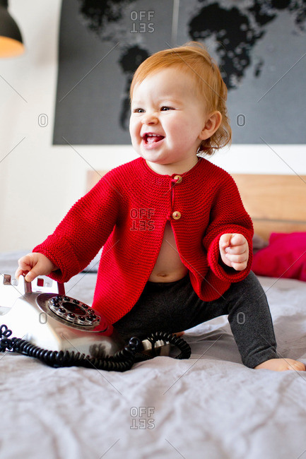 Baby girl sitting on bed playing with landline telephone