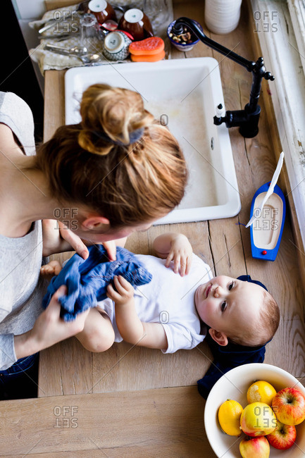 Overhead view of woman undressing baby son for bath in kitchen sink