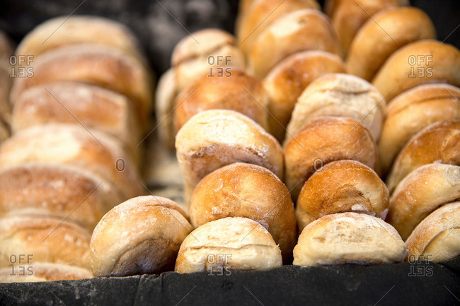 Tray of fresh bread rolls on cooperative food market stall