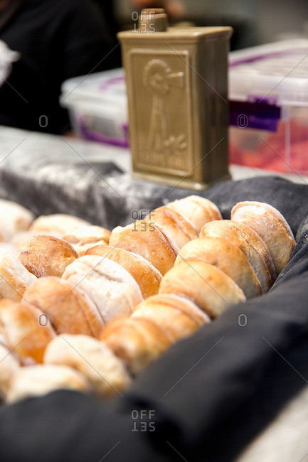 Rows of fresh bread rolls in tray on cooperative food market stall