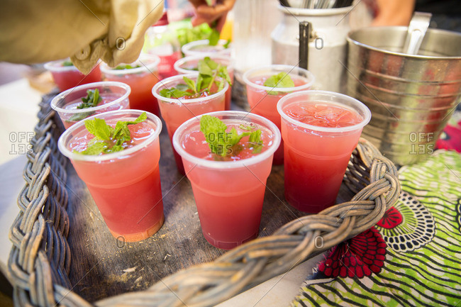 Stall holder garnishing fruit drinks with mint on cooperative food market stall