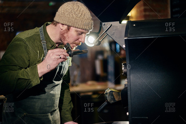 Male coffee shop owner at coffee machine smelling coffee