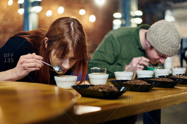 Coffee shop team smelling bowls of coffee and coffee beans at tasting