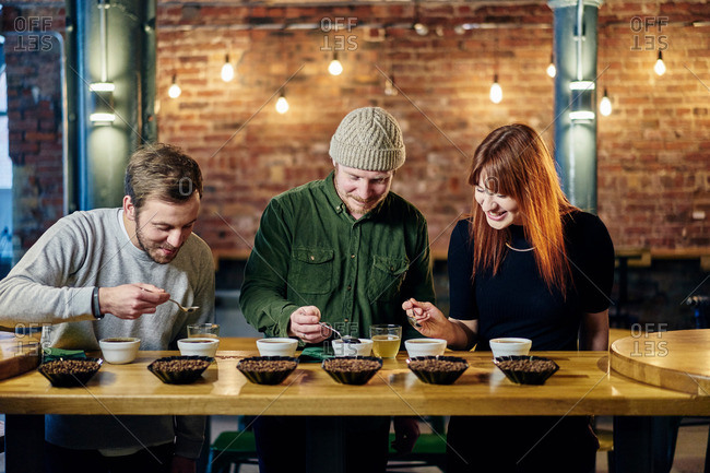 Coffee shop team tasting bowls of coffee and coffee beans