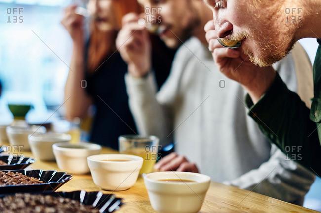 Team tasting bowls of coffee at coffee shop tasting