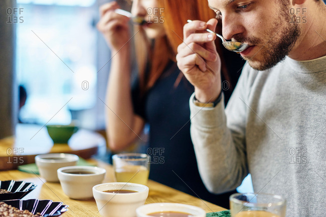 Man and woman tasting bowls of coffee at coffee shop tasting