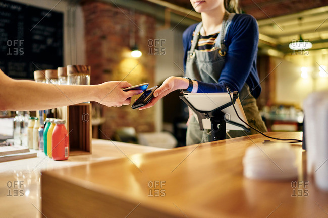 Female barista taking smartphone contactless payment from coffee shop customer