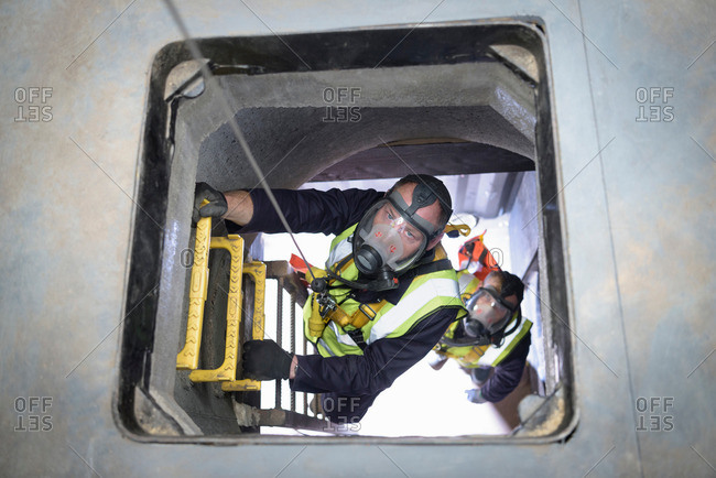 Apprentice builders climbing in confined space in training facility