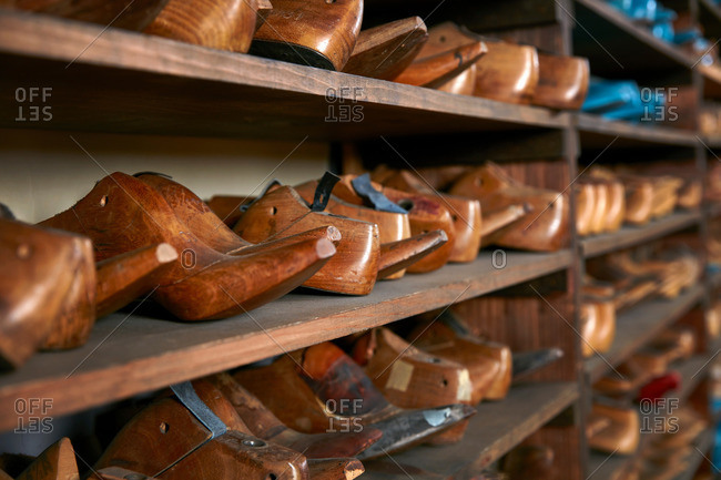 Rows of old wooden shoe lasts on shelves in traditional shoe shop, selective focus