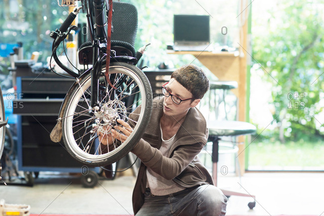 Woman in bicycle workshop repairing wheel on recumbent bicycle