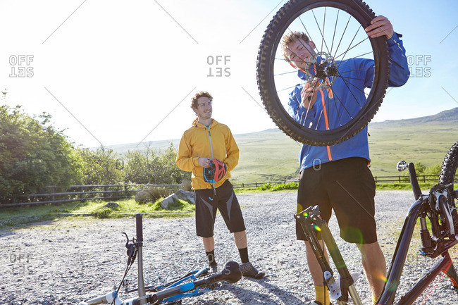 Cyclist attaching bicycle wheel to bicycle