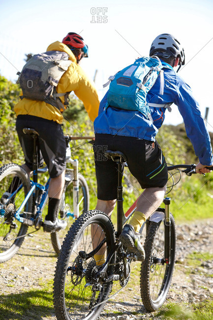 Rear view of cyclists cycling on dirt track