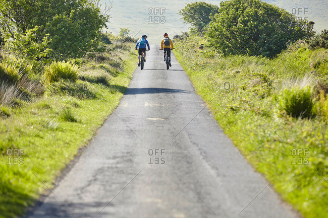 Rear view of cyclists cycling on rural road