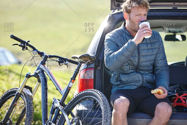 Cyclist sitting on car boot drinking from disposable cup