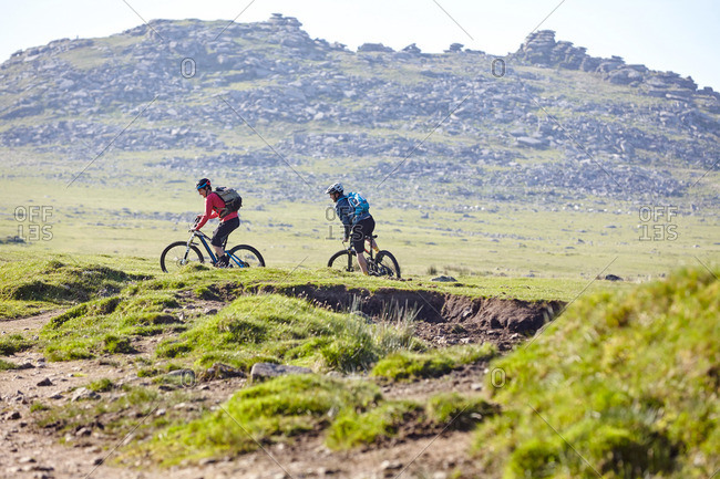 Cyclists cycling on hillside - Offset