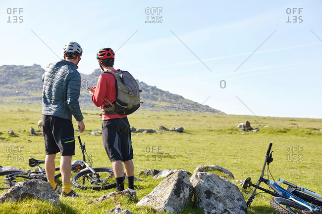 Cyclists on hillside chatting - Offset