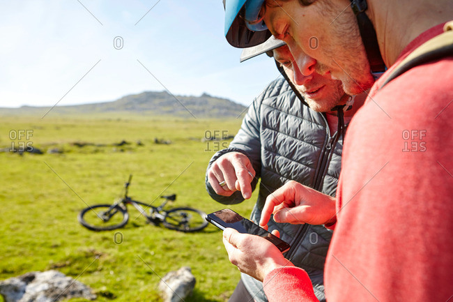 Cyclists on hillside looking at smartphone