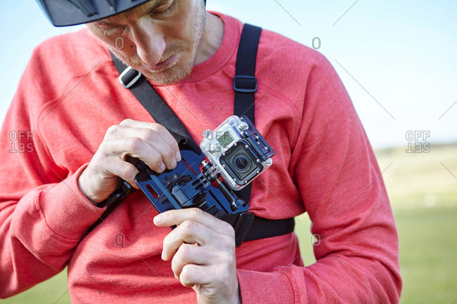 Man attaching action camera to chest