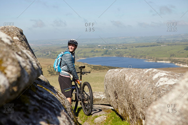 Cyclist with bicycle on rocky outcrop