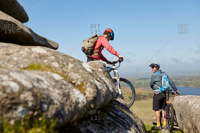 Cyclists with bicycles on rocky outcrop