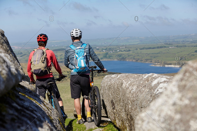 Back view of cyclists with bicycles on rocky outcrop