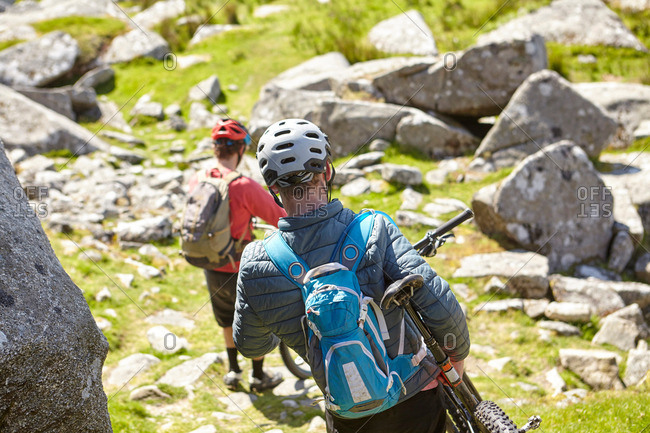 Cyclists carrying bicycles on rocky outcrop