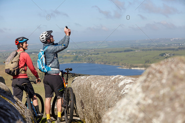 Cyclists with bicycles on rocky outcrop taking photo