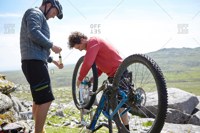 Cyclists fixing bicycle on mountainside