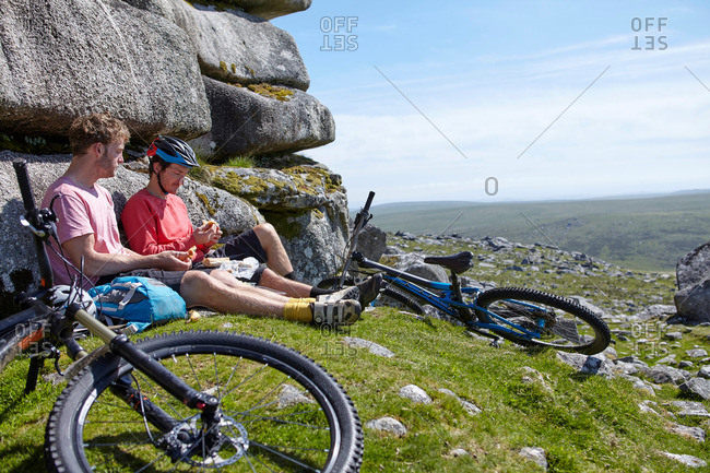 Cyclists sitting on rocky outcrop having picnic