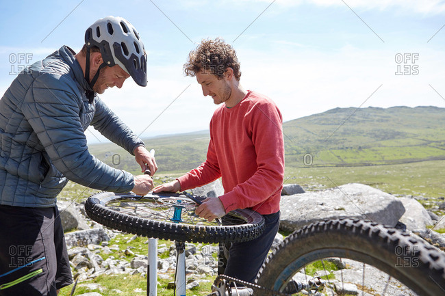 Cyclists repairing bicycle on mountainside