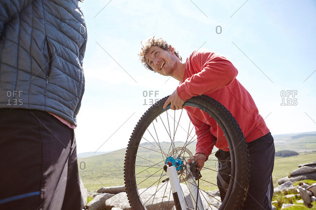 Cyclists repairing bikes on mountainside
