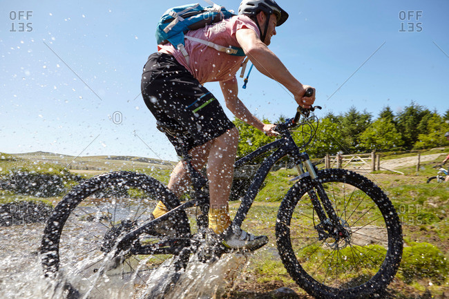 Cyclists cycling through water - Offset