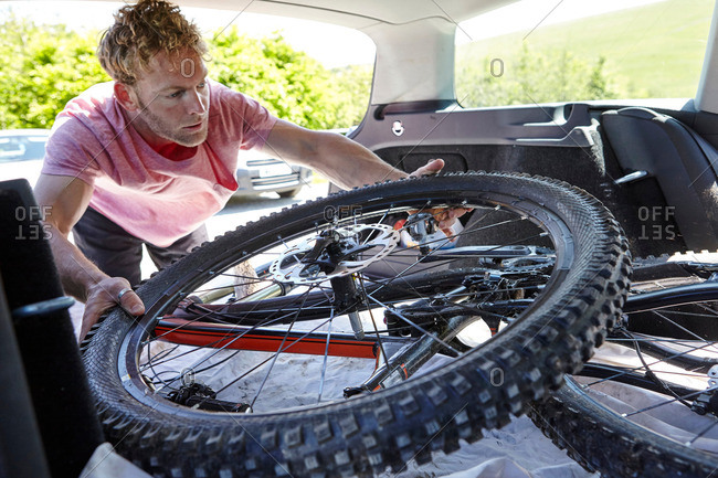 Cyclist placing bicycle in car trunk