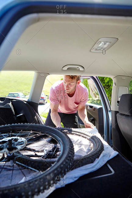 Cyclist placing bike in car trunk