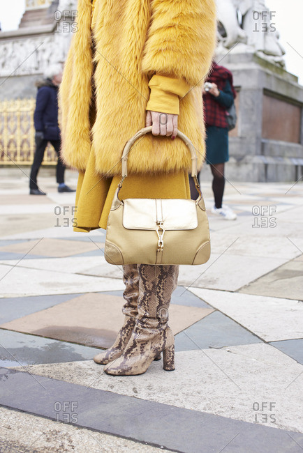 Woman in yellow fur coat holding handbag, vertical, crop