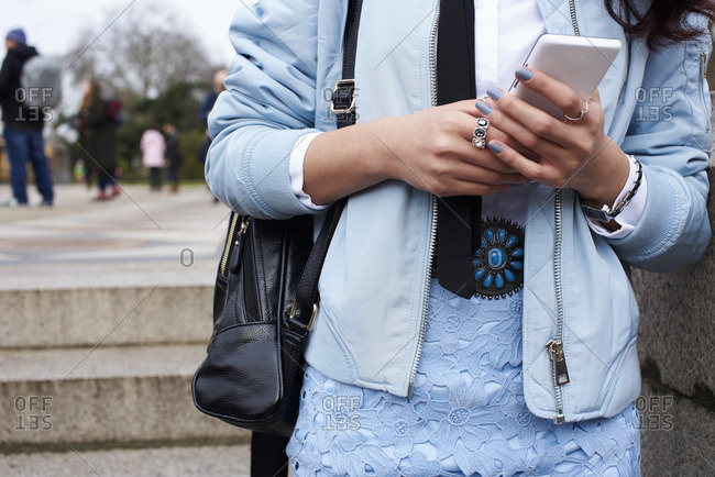 Mid section of woman wearing pastel blue using smartphone