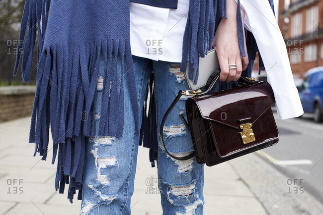 Woman in ripped jeans holding handbag in street, mid section