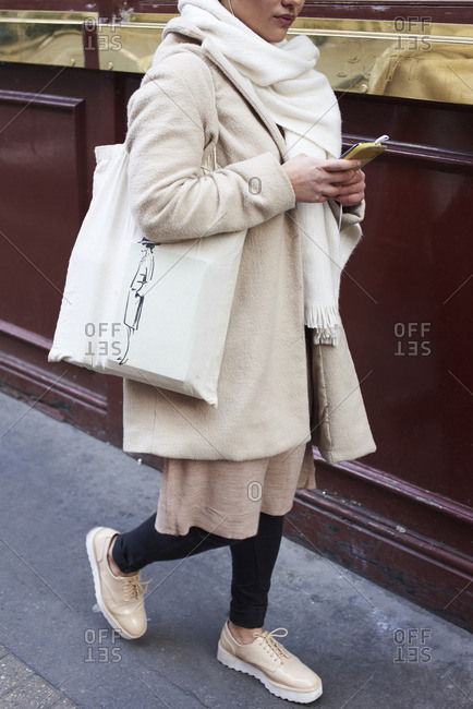 Woman with cream coat, shawl and bag using phone in street