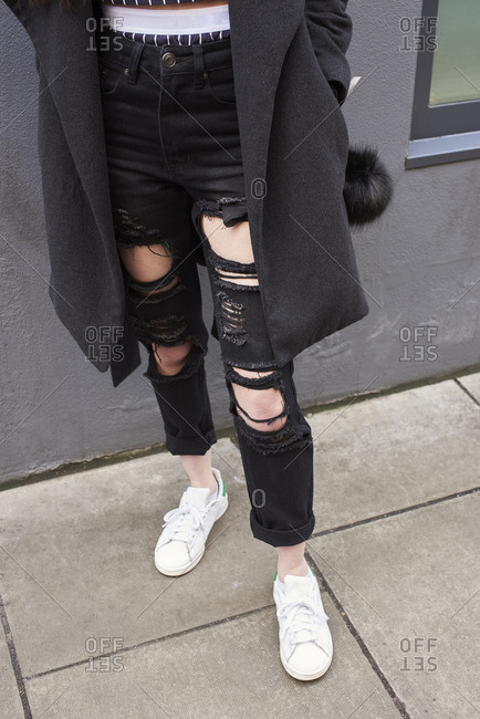 Woman wearing ripped black jeans and sports shoes, vertical
