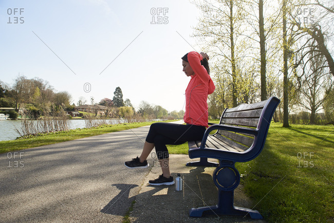 Young Woman Sitting On Park Bench Stretching Before Exercise