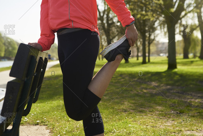 Young Woman Stretching On Park Bench Before Exercise