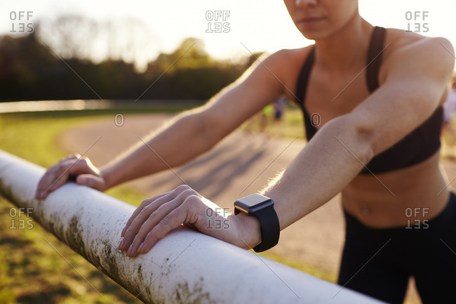 Young Woman Wearing Activity Tracker Stretches Before Run